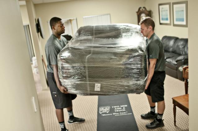 两个搬家公司的工人在搬运沙发